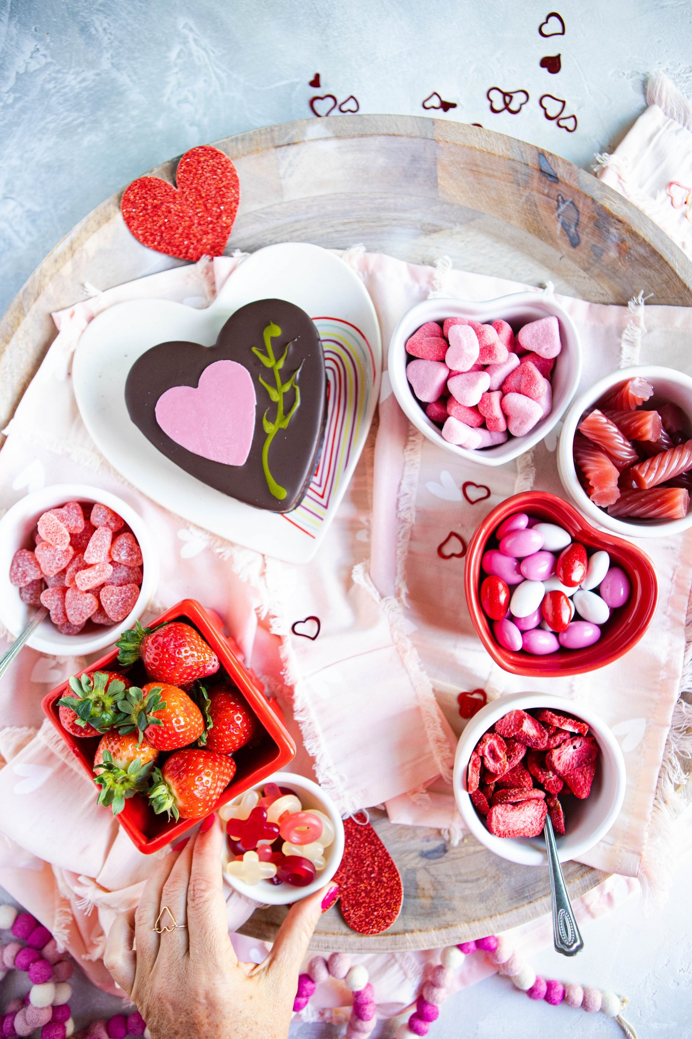 woman's hand placing Valentine's day candy on a wooden tray, surrounded by other sweets