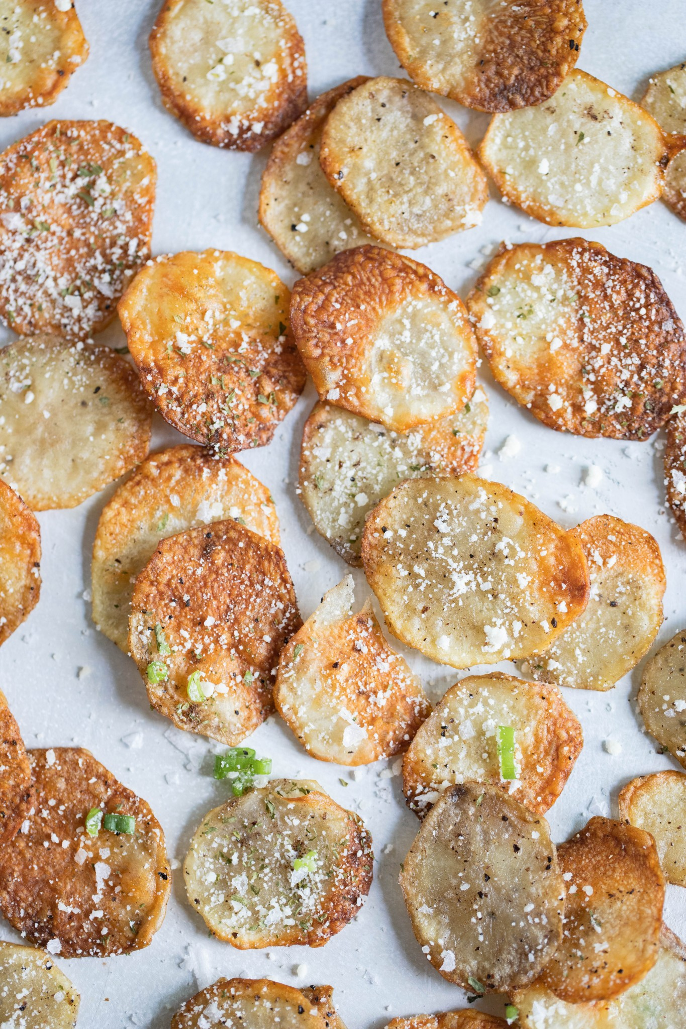 homemade potato chips in air fryer sprinkled with truffle seasoning and parmesan cheese