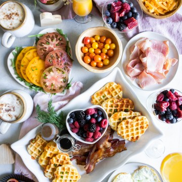 savory waffles breakfast spread with fruit, herbs, tomatoes, bacon and orange juice