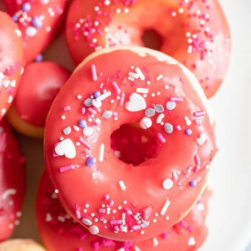 valentine donuts in air fryer sprinkled with red glaze and heart sprinkles
