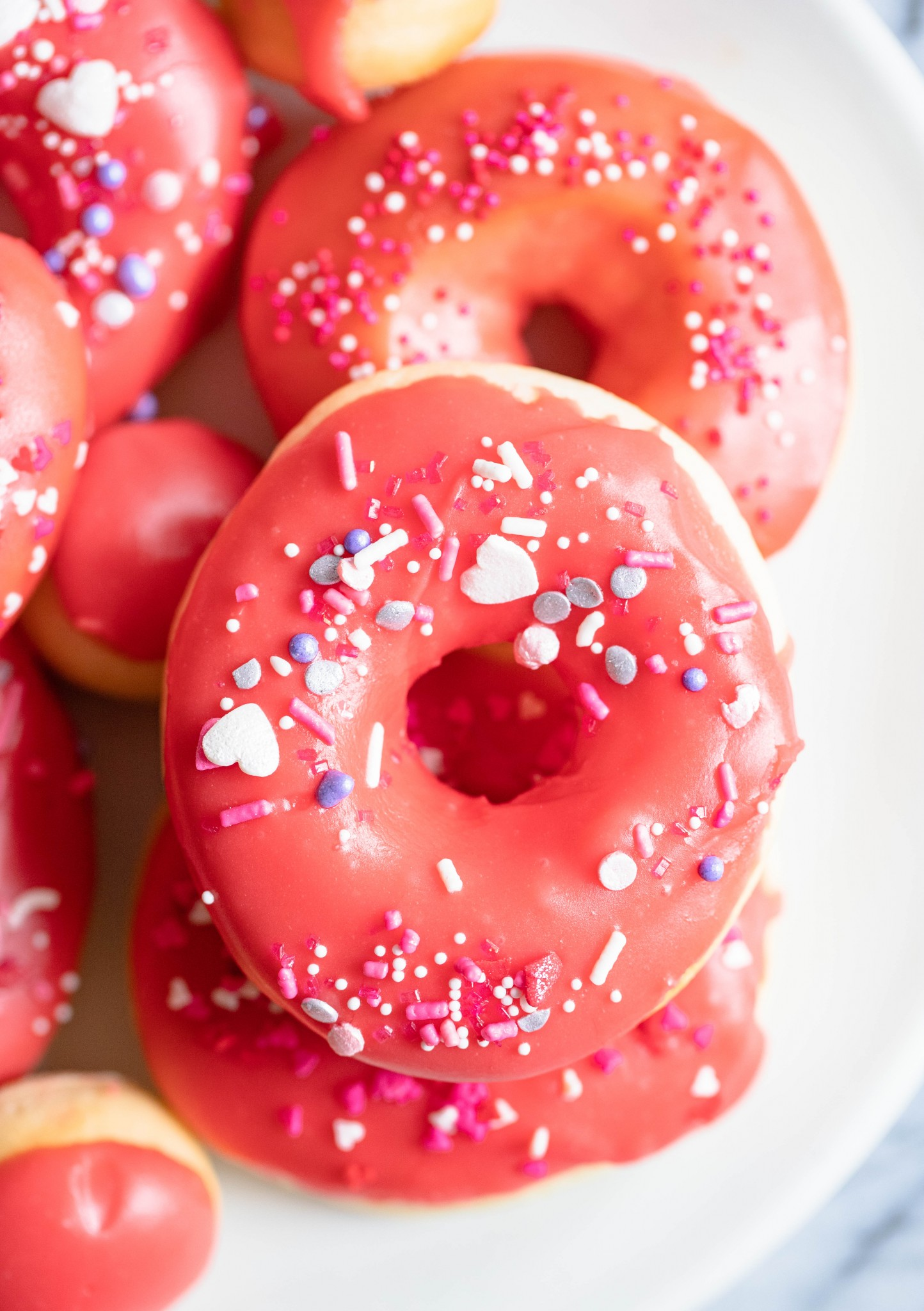 donuts sprinkled with red glaze and heart sprinkles