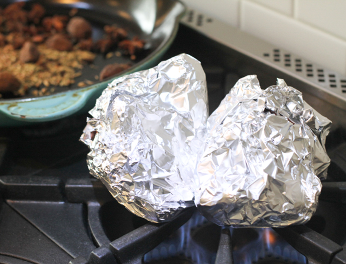 onion and ginger wrapped in tin foil set on an open flame on the stove