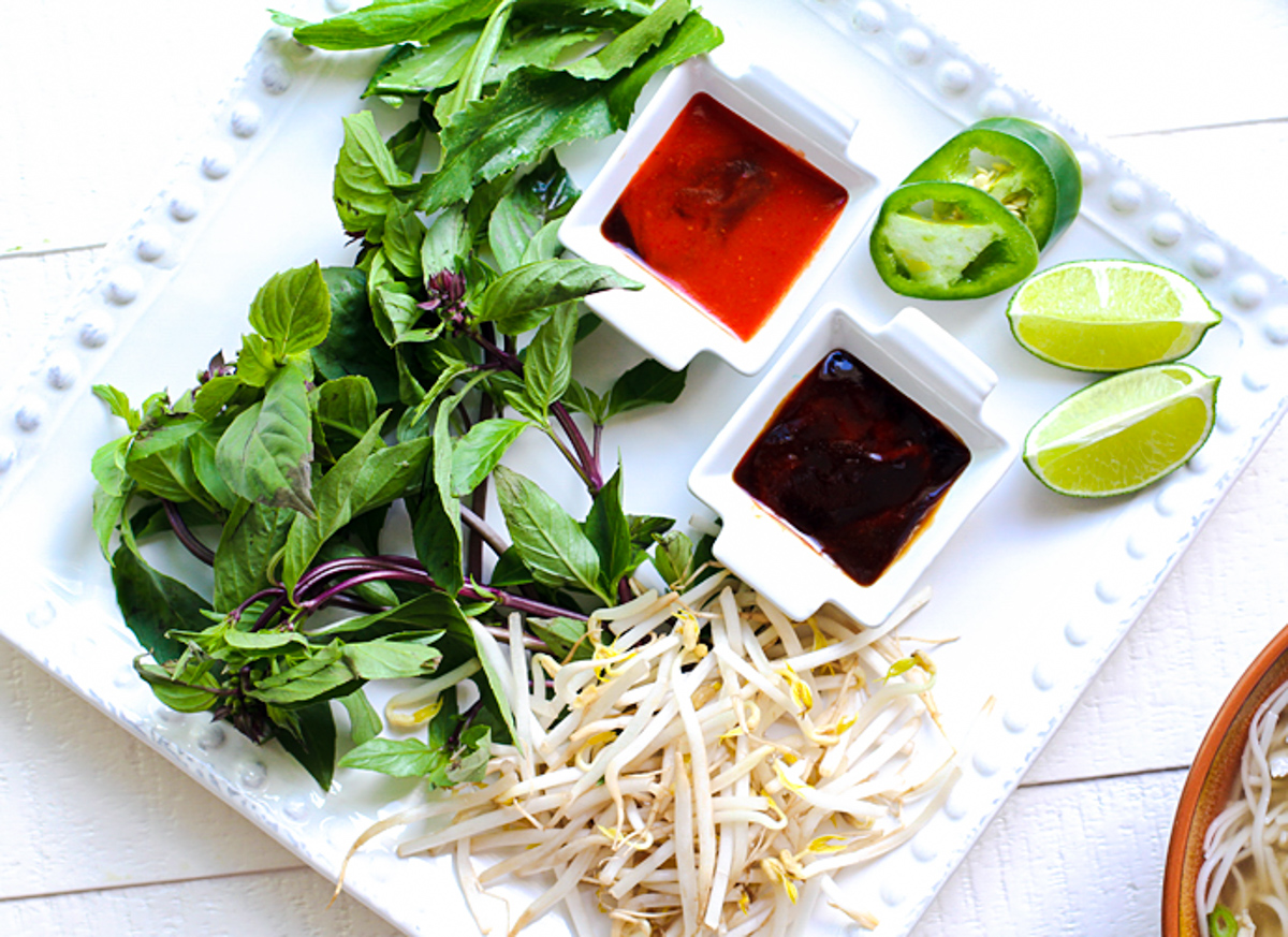 white plate filled with Thai basil, jalapeno, limes, bean sprouts, sriracha and hoisin sauce