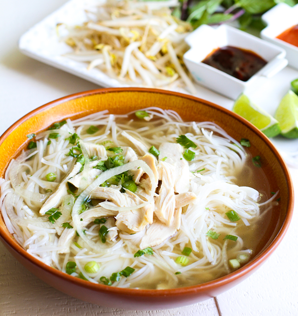 bowl filled with cooked rice noodles and pho ga broth