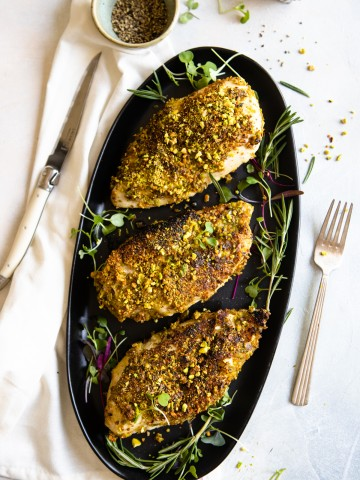 platter of chicken breasts with pistachio crust on a black platter and greens