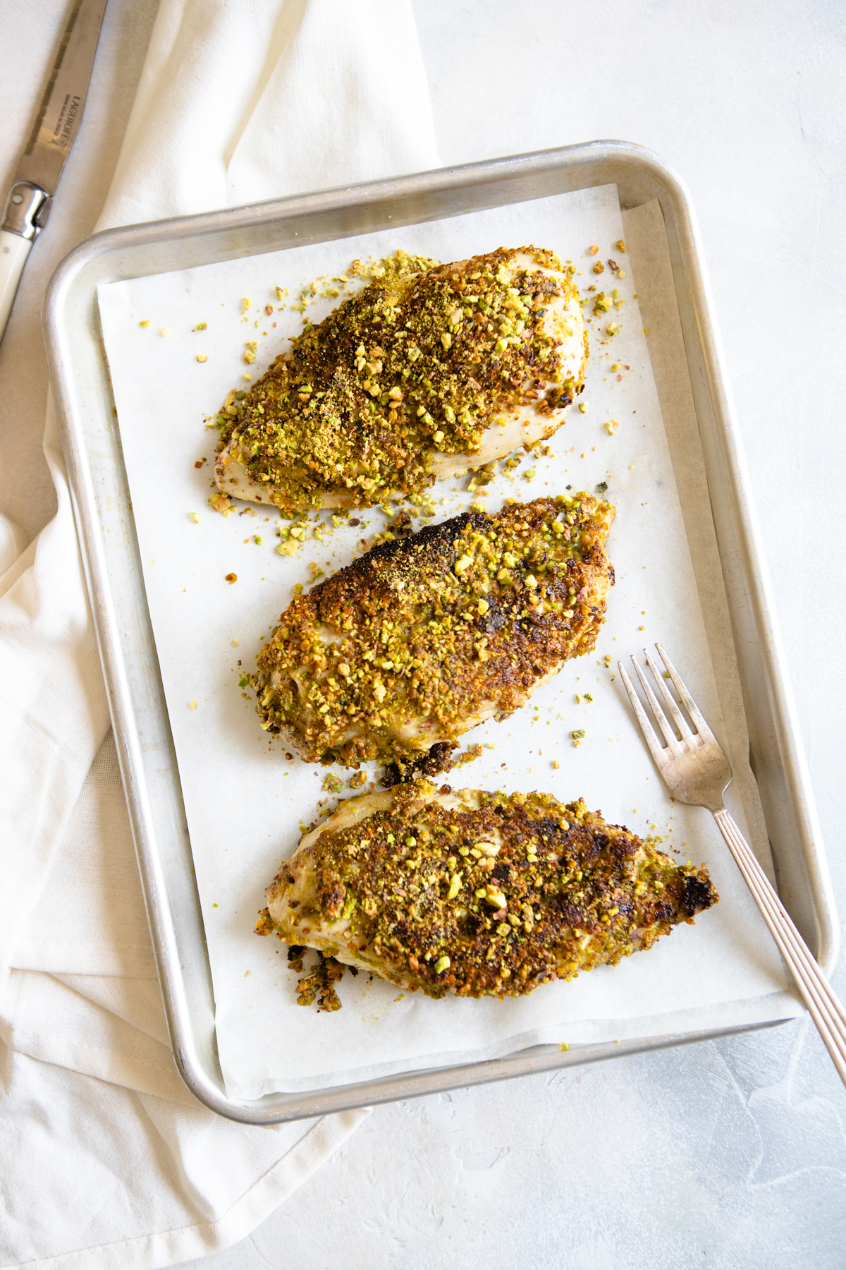 3 baked chicken breasts with pistachio topping placed on a baking sheet